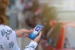 Vrouw die smartphone app gebruiken om voor parkeren te betalen stock foto