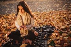 Vrouw die smartphone in daling gebruiken De herfstmeisje die slim telefoongesprek in het gebladerte van de zongloed hebben Portre royalty-vrije stock foto