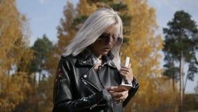Vrouw die smartphone in de herfstpark gebruiken stock footage