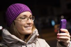 Vrouw die smartphone in de 's nachts stad gebruiken Stock Afbeeldingen