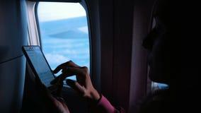 Vrouw die smartphone en wijzerplaten met behulp van een bericht op de telefoon op het vliegtuig tegen het venster tijdens de vluc stock videobeelden
