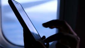 Vrouw die smartphone en wijzerplaten tijdens de vlucht binnen met behulp van een bericht op de telefoon op het vliegtuig tegen he stock videobeelden