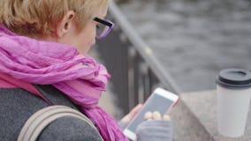 Vrouw die smartphone gebruiken bij rivier stock videobeelden