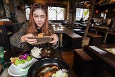 Vrouw die smartphone gebruiken die een foto van voedsel in restaurant nemen royalty-vrije stock afbeelding