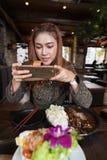Vrouw die smartphone gebruiken die een foto van voedsel in restaurant nemen stock afbeeldingen