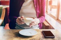 Vrouw die smartphone in koffiewinkel gebruiken Stock Foto's