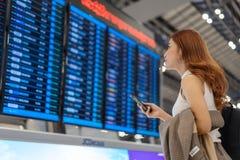 Vrouw die smartphone met de raad van de vluchtinformatie gebruiken bij luchthaven stock fotografie