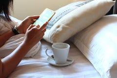 Vrouw die smartphone op bed gebruiken stock afbeelding