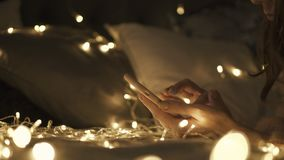 Vrouw die smartphone op het bed gebruiken Het gebruiken van telefoon, sociaal netwerken Kerstmislichten op achtergrond stock videobeelden