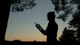 Vrouw die smartphone in park na zonsondergang gebruiken Royalty-vrije Stock Afbeelding