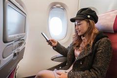 Vrouw die smartphone in vliegtuig tijdens de vlucht tijd gebruikt royalty-vrije stock foto's