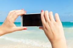 Vrouw die smartphone voor het nemen van openluchtfoto gebruiken Stock Afbeeldingen