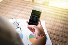 Vrouw die smartphonegrafiek op het scherm tonen Royalty-vrije Stock Foto's