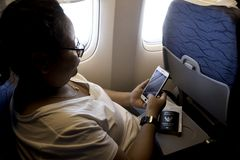 vrouw die smartphonevliegtuig met behulp van stock foto's
