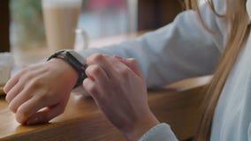 Vrouw die smartwatch touchscreen wearable technologieapparaat met behulp van close-up Mooi meisje die gebaren op een smartwatch m stock footage