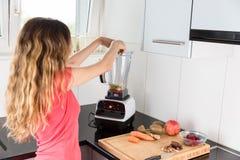 Vrouw die smoothie in de keuken maken Royalty-vrije Stock Afbeelding