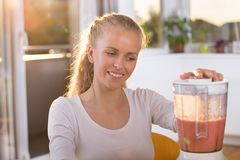 Vrouw die smoothie in mixer voorbereidingen treffen royalty-vrije stock afbeelding
