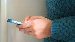 Vrouw die sms op blauwe telefoon als mededeling schrijven stock footage