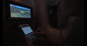 Vrouw die SMS typen tijdens nachtvlucht stock video