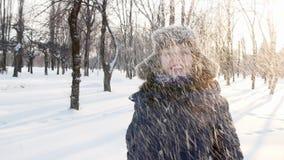 Vrouw die sneeuw over zich werpen en het glimlachen in het de winterpark stock footage