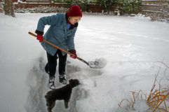 Vrouw die sneeuw schept royalty-vrije stock afbeeldingen