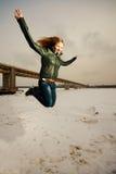 Vrouw die in sneeuw springt royalty-vrije stock afbeelding
