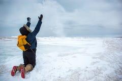 Vrouw die sneeuw werpen terwijl het knielen op bevroren golf Stock Afbeelding