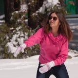 Vrouw die sneeuwbal werpt Stock Afbeeldingen