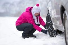 Vrouw die sneeuwketting installeren stock afbeelding