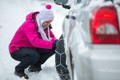 Vrouw die sneeuwkettingen zetten royalty-vrije stock afbeeldingen
