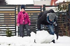 Vrouw die sneeuwman maken Stock Afbeeldingen
