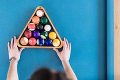 Vrouw die snookerballen met houten driehoeksrek schikken royalty-vrije stock foto's