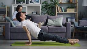 Vrouw die sociale media controleren die laptop met behulp van terwijl echtgenoot die yoga het uitwerken doen stock footage