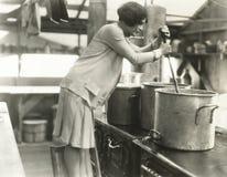 Vrouw die in soepkeuken werken Stock Foto's