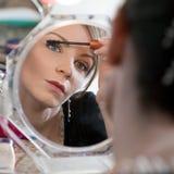 Vrouw die spiegel bekijkt Stock Foto