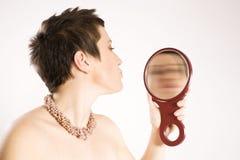 Vrouw die in spiegel kijkt Stock Foto