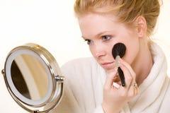 Vrouw die in spiegel kijkt Stock Afbeelding