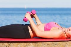 Vrouw die sporten in openlucht met domoren doen Stock Foto