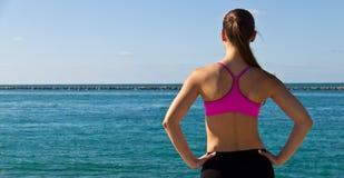 Vrouw die in sportenbustehouder de oceaan bekijken Stock Foto