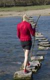 Vrouw die springplanken gebruiken om een rivier te kruisen Royalty-vrije Stock Afbeelding