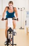 Vrouw die stationaire fiets in gezondheidsclub berijdt royalty-vrije stock afbeelding