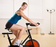 Vrouw die stationaire fiets in gezondheidsclub berijdt stock foto's