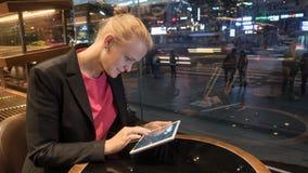 Vrouw die stootkussen in koffie gebruiken door venster met stadsmening Stock Afbeeldingen