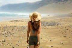 Vrouw die in strohoed op een tropisch strand lopen die dat als een ongelooflijk martian landschap kijken stock foto