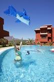 Vrouw die stuk speelgoed opblaasbare dolfijn in lucht werpt Stock Foto
