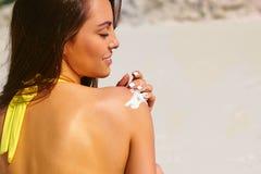 Vrouw die sunblock room op mooi tropisch strand toepassen royalty-vrije stock afbeeldingen