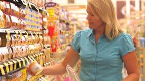 Vrouw die in supermarkt winkelen stock videobeelden