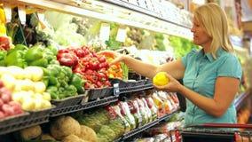 Vrouw die in supermarkt winkelen stock footage