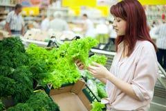 Vrouw die in supermarkt winkelt Stock Foto