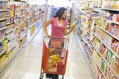 Vrouw die in supermarktdoorgang winkelt Stock Afbeeldingen